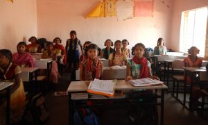 Cute Indian schoolgirls seated at desks