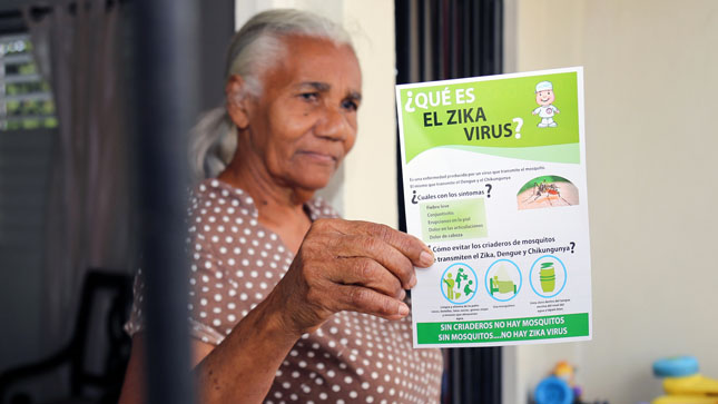 "Woman holding ""What is the Zika virus?"" handout."