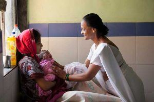 Woman helping woman and newborn; Kiran Thejaswi/Jhpiego, 2014