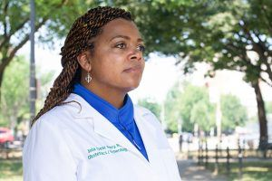 Dr. Joia Crear-Perry, wearing a white doctor's coat, stands outside.